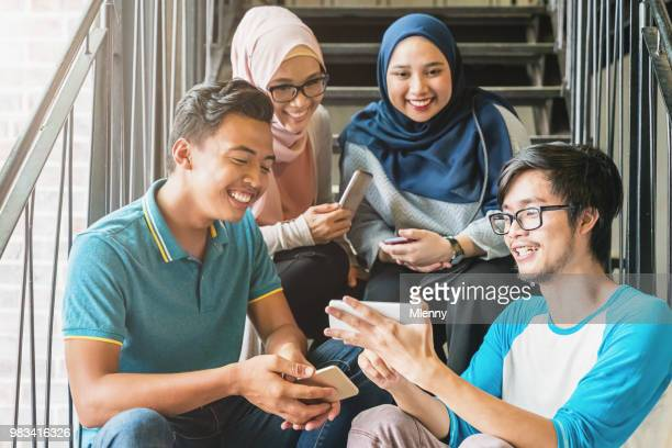 Malaysian friends watching video on mobile phone