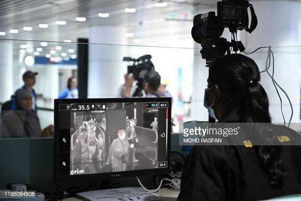 Malaysian health officer screens arriving passengers with a thermal scanner at Kuala Lumpur International Airport in Sepang on January 21, 2020 as...