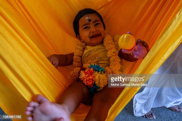 Malaysian Hindus devotees carry a baby inside a hammock during their pilgrimage to the sacred Batu Caves temple during Thaipusam festivals on January...