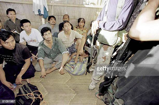 Malaysian Hostages Are Guarded By Two Muslim Rebels Armed With Assault Rifles While Being Detained At The Abu Sayyaf Mountain Camp On Jolo Island In...