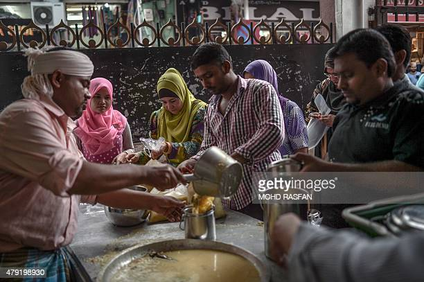 A Malaysian Indian Muslim man distributes the popular dish 'Bubur Lambuk' at Masjid India during the Muslim holy fasting month of Ramadan in Kuala...