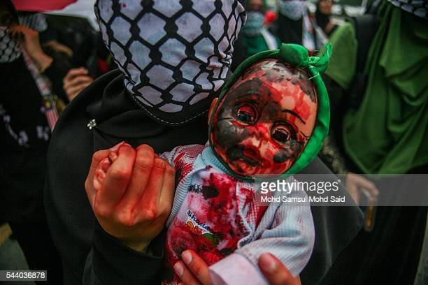 Malaysian Islamic NGO from AlQuds Malaysia hold a dolls as a symbolic of Palestinian died in front of the United States Embassy during a...