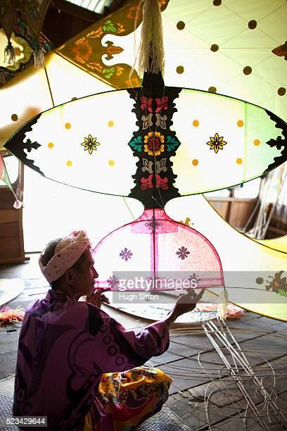 malaysian kite maker working on kite in his work shop - hugh sitton bildbanksfoton och bilder