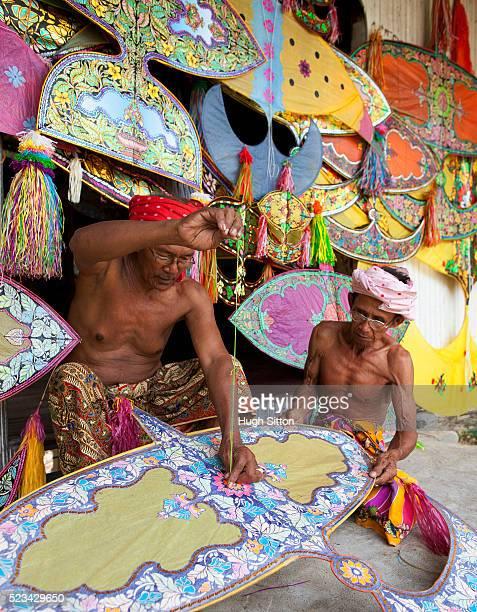malaysian kite makers working on colorful traditional kites - hugh sitton stock-fotos und bilder