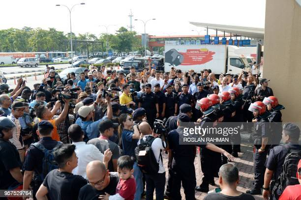 Malaysian Light Strike Force police stand guard as members of the media and public gather outside the Skypark terminal at Sultan Abdul Aziz Shah...