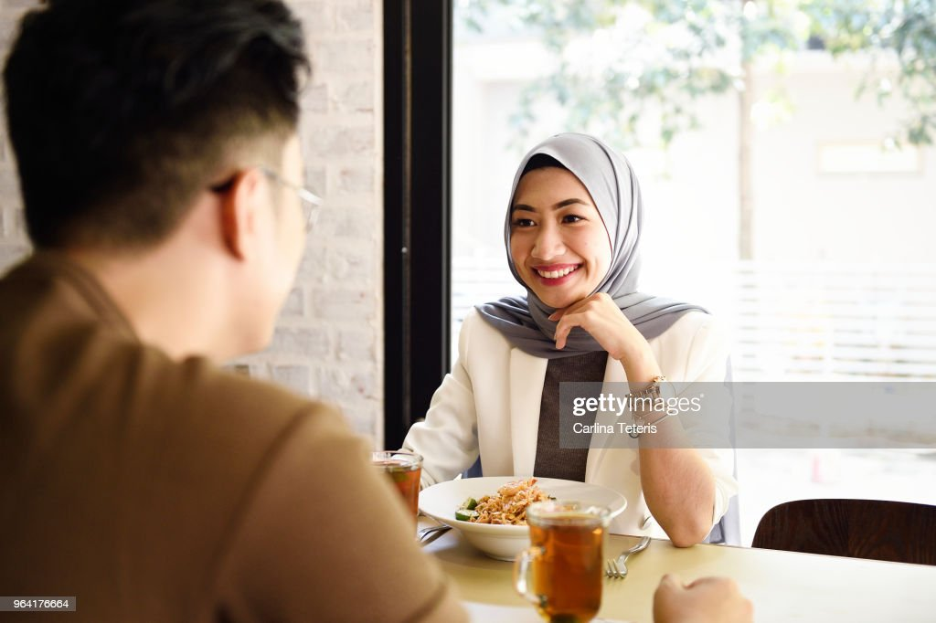 Malaysian man and woman having lunch in a restaurant : Stock Photo