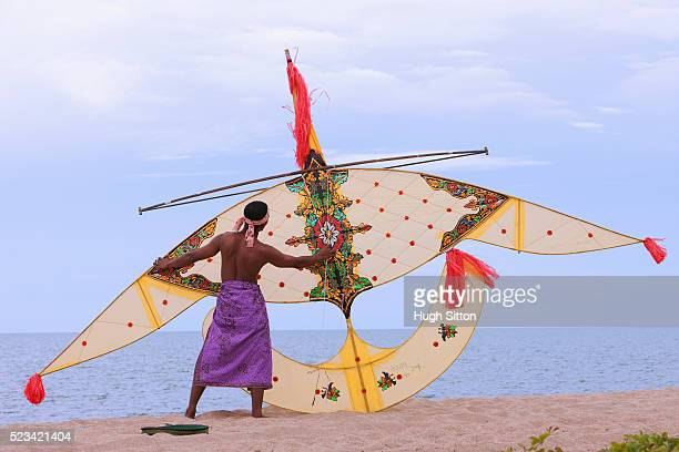 malaysian man holding traditional handmade kite on beach - hugh sitton stock pictures, royalty-free photos & images