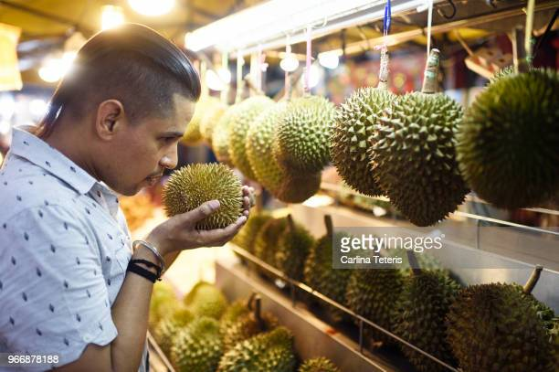 malaysian man selecting durian fruit - one night stand stock-fotos und bilder