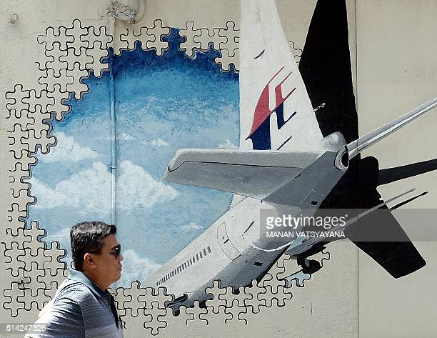 A Malaysian man walks in front of a mural of missing Malaysia Airlines MH370 plane in a backalley in Shah Alam on March 8 2016 Malaysia and Australia...