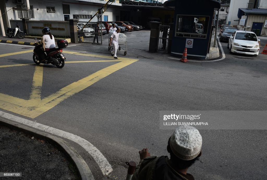 A Malaysian man watches as hospital workers move a body cart through the gate of the forensics wing of the Hospital Kuala Lumpur, where the body of Kim Jong-Nam is being held, in Kuala Lumpur on March 14, 2017. The killing of the half-brother of North Korea's leader Kim Jong-Un last month in Kuala Lumpur International Airport with VX nerve agent triggered a bitter standoff between the previously friendly Asian nations, which have expelled each other's ambassador and refused to let their citizens leave. /