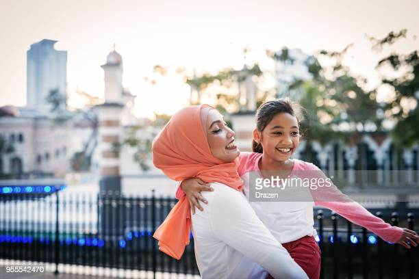 malaysian mature woman with daughters after school - muslim mother stock pictures, royalty-free photos & images