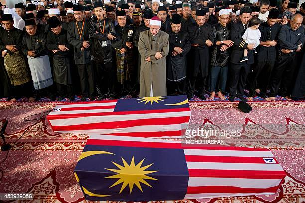 Malaysian Muslim and family members offer special prayers for the remains of copilot Ahmad Hakimi Hanapi and flight attendant Nur Shazana Mohamed...