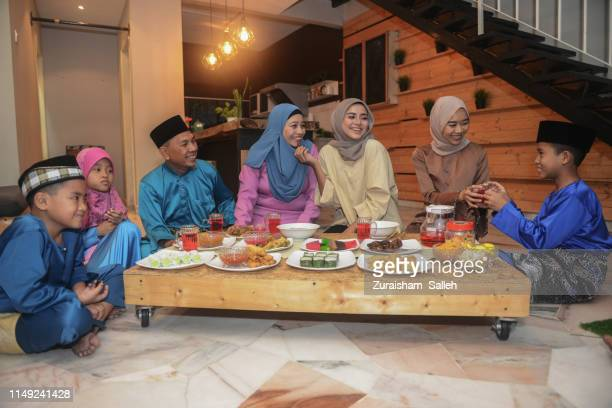 malaysian muslim family celebrating eid-ul-fitr at home - eid ul fitr stock pictures, royalty-free photos & images