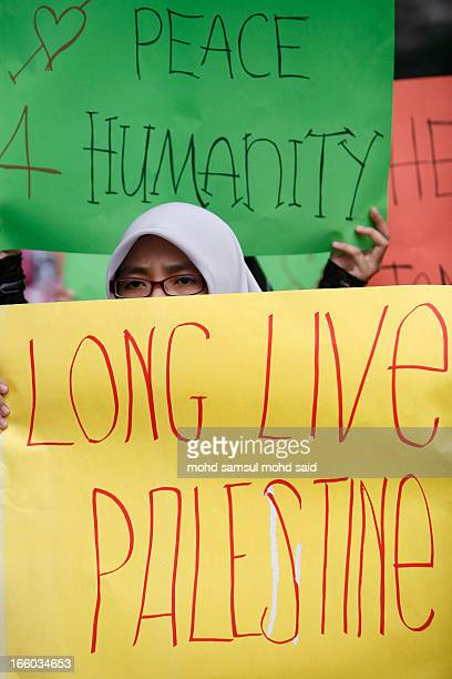 Malaysian muslim hold the playcard during a protest against Israel's military operation in the Gaza Strip, in front of the U.S. Embassy in Kuala...