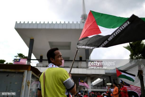 A Malaysian Muslim man waves a Palestinian flag during a solidarity protest after Friday prayers outside the National Mosque in Kuala Lumpur on July...