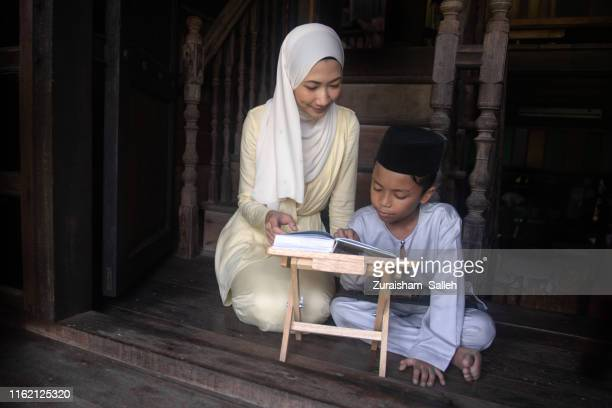 malaysian muslim woman and a boy reading koran together at home - beautiful ramadan stock pictures, royalty-free photos & images