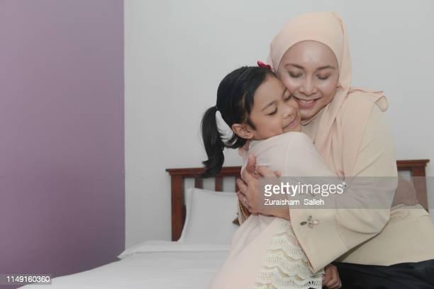 malaysian muslim woman hugs her daughter during eid-ul-fitr celebration - beautiful ramadan stock pictures, royalty-free photos & images