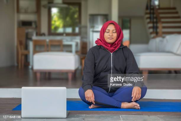 malaysian muslim woman practicing guided meditation via laptop at her home - epidemic stock pictures, royalty-free photos & images