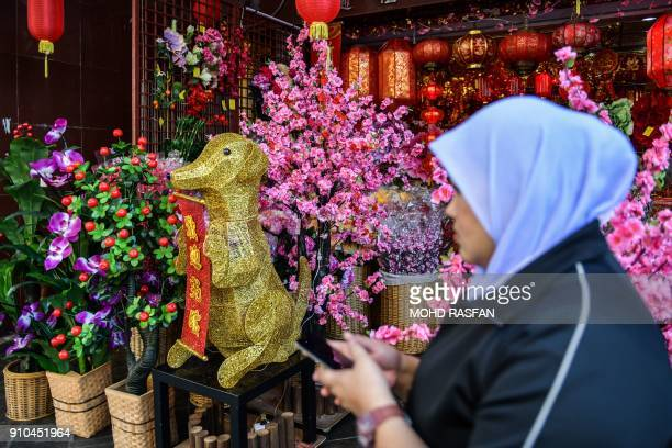 A Malaysian Muslim woman walks past a golden canine statue ahead of the Lunar New Year celebrations in Kuala Lumpur's Chinatown on January 26 2018 As...