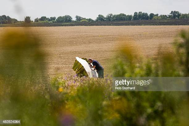 Malaysian official inspects wreckage of Malaysia Airlines flight MH17 during monitoring by investigators from Malaysia and the Organization for...