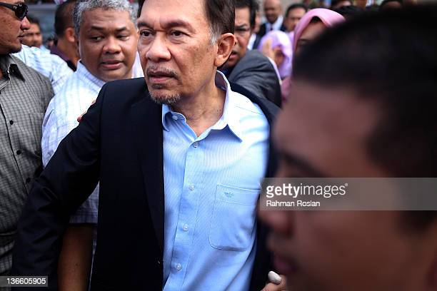Malaysian opposition leader Anwar Ibrahim greets supporters after he was acquited from his sodomy charge outside the High Court on January 9 2012 in...