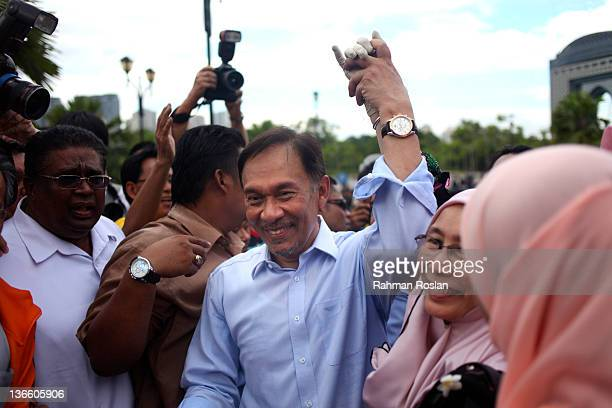 Malaysian opposition leader Anwar Ibrahim holds the hand of his wife Wan Azizah after he was acquited from his sodomy charge outside the High Court...