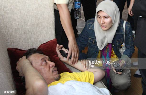 Malaysian opposition leader Anwar Ibrahim is comforted by his daughter Nurul Izzah after he felt unwell and fell on the pavement following a tear gas...