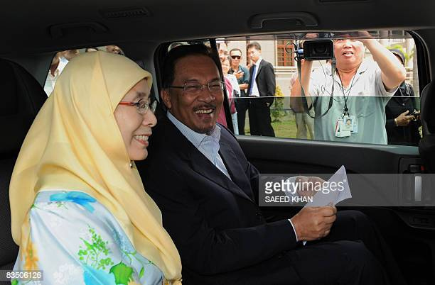 Malaysian opposition leader Anwar Ibrahim smiles while leaving the court along with his wife Wan Azizah Wan Ismail in Kuala Lumpur on October 31 2008...