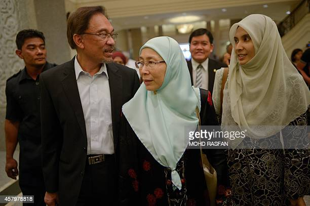 Malaysian Opposition leader Anwar Ibrahim talks to his daughter Nurul Izzah as his wife Wan Azizah listens as they leave the court of appeals in...