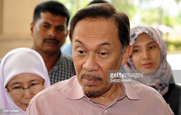 Malaysian opposition leader Anwar Ibrahim talks to media as he arrives at court along with his wife Wan Azizah and daughter Nurul Izzah in Kuala...