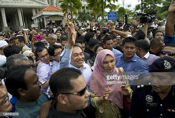 Malaysian opposition leader Anwar Ibrahim waves to his supporters along with his daughter Nurul Izzah following the court verdict in Kuala Lumpur on...