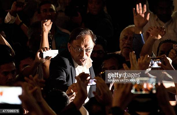 Malaysian opposition leader Anwar Ibrahim waves to supporters as he leaves the court of appeals in Putrajaya outside Kuala Lumpur on March 7 2014...