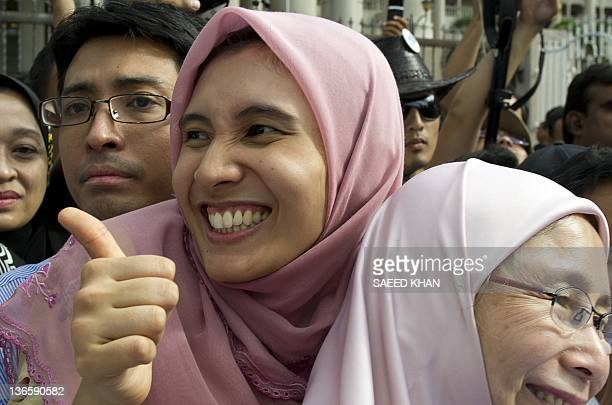 Malaysian opposition leader Anwar Ibrahim's daughter Nurul Izzah along with mother Wan Azizah celebrates the court decision in his father's verdict...