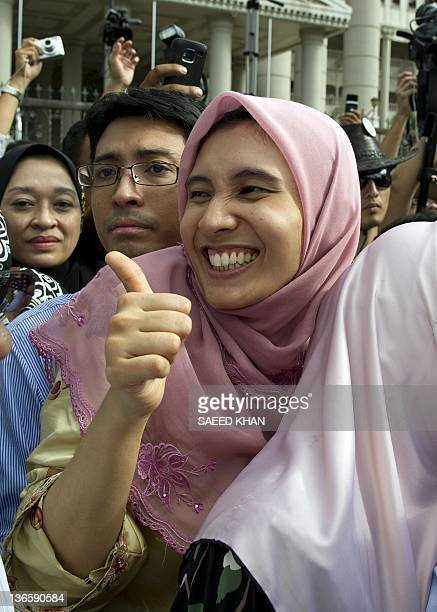 Malaysian opposition leader Anwar Ibrahim's daughter Nurul Izzah celebrates the court decision in his father's verdict outside the court in Kuala...
