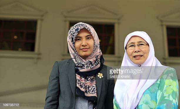 Malaysian opposition leader Anwar Ibrahim's wife Wan Azizah and daughter Nurul Izzah wait for him on the stairs of the court in Kuala Lumpur on March...