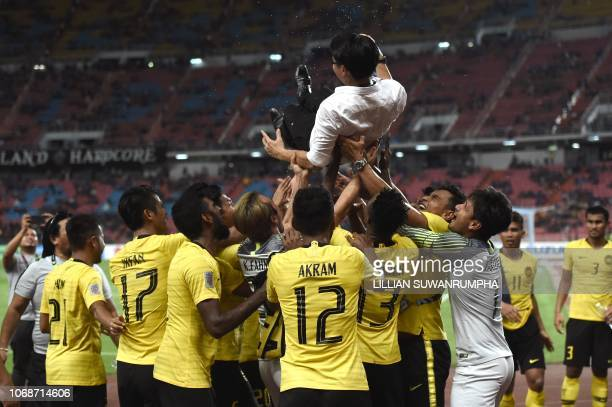 Malaysian players celebrate with coach Tan Cheng Hoe after a nailbiting draw with Thailand during the second leg of the AFF Suzuki Cup 2018 semifinal...