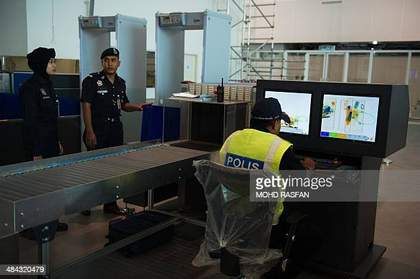 A Malaysian police officer looks at the screena of xray machines at the new lowcost airport Kuala Lumpur International Airport 2 during the...