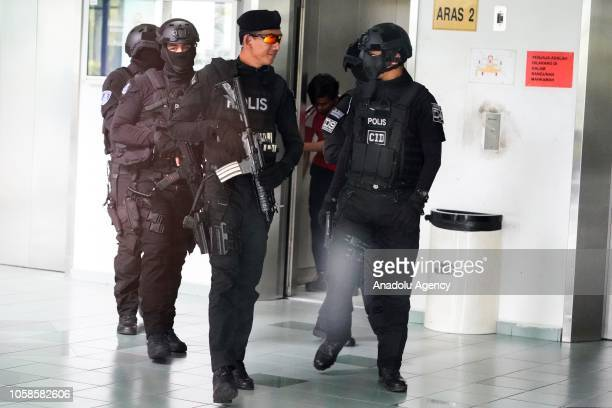 Malaysian Police officers stand guard as Indonesian Siti Aisyah and Vietnamese Doan Thi Huong arrive at the court session for their management case...