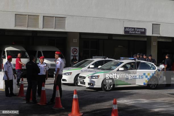 Malaysian police officers stand outside the forensic department of Putrajaya Hospital in Putrajaya outside Kuala Lumpur on February 15 where the body...