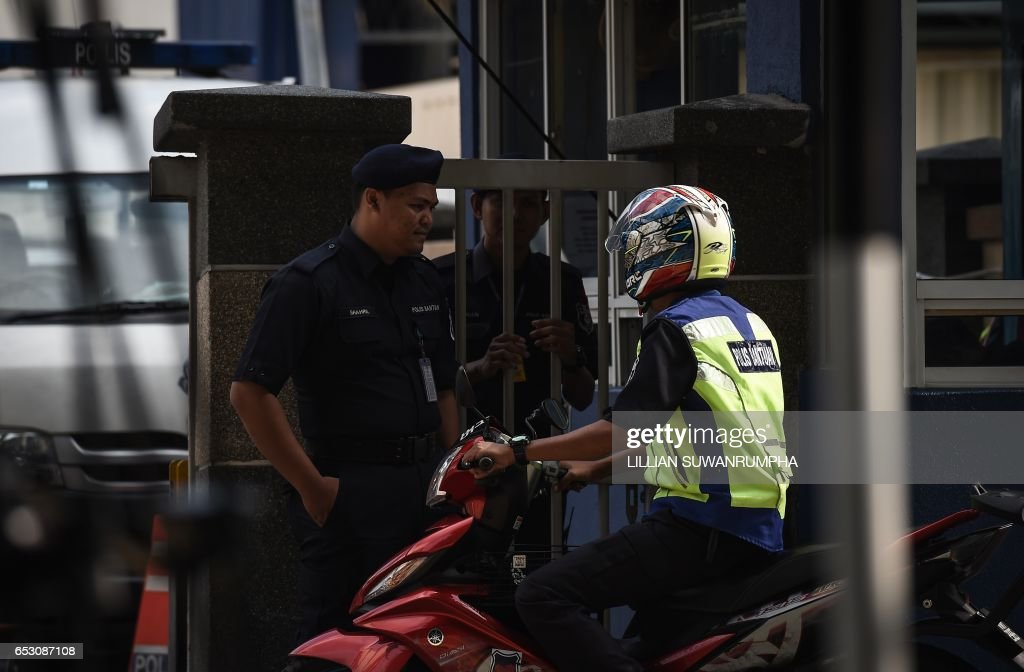 Malaysian policemen talk to each other at the gate of the forensics wing of the Hospital Kuala Lumpur, where the body of Kim Jong-Nam is being held, in Kuala Lumpur on March 14, 2017. The killing of the half-brother of North Korea's leader Kim Jong-Un last month in Kuala Lumpur International Airport with VX nerve agent triggered a bitter standoff between the previously friendly Asian nations, which have expelled each other's ambassador and refused to let their citizens leave. /