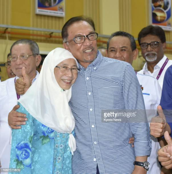 Malaysian politician Anwar Ibrahim celebrates with his wife and the country's Deputy Prime Minister Wan Azizah Wan Ismail after winning a landslide...