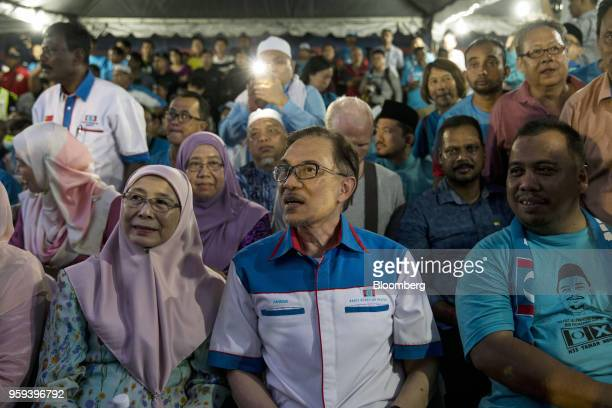 Malaysian politician Anwar Ibrahim center sits with his wife Wan Azizah binti Wan Ismail Malaysia's deputy prime minister left at a Pakatan Harapan...