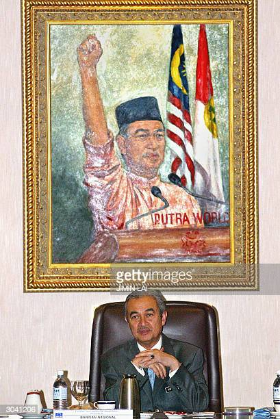 Malaysian Prime Minister Abdullah Ahmad Badawi sits below a selfportrait during a meeting with fellow members of the National Front Coalition prior...