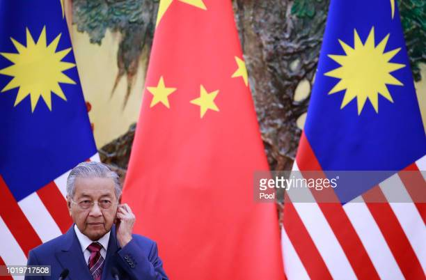 Malaysian Prime Minister Mahathir Mohamad adjusts his earphones during a press conference at the Great Hall of the People in Beijing, China, 20...