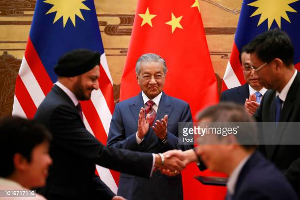 Malaysian Prime Minister Mahathir Mohamad and his Chinese counterpart Li Keqiang claps as delegates exchange documents during a signing ceremony at...