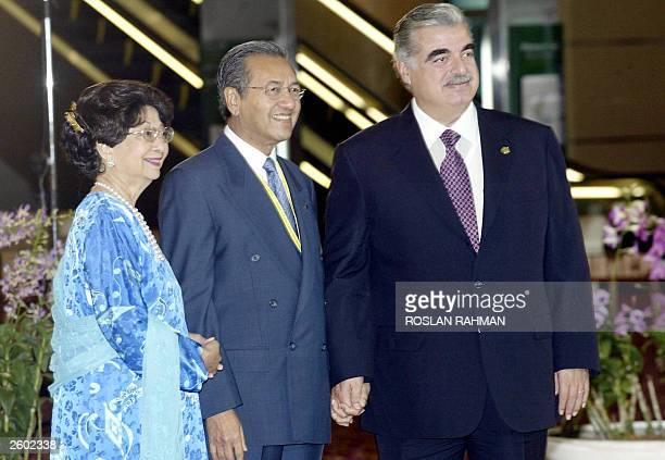 Malaysian Prime Minister Mahathir Mohamad and his wife Siti Hasmah pose with Lebanese Prime Minister Rafiq Hariri before the opening of a summit of...