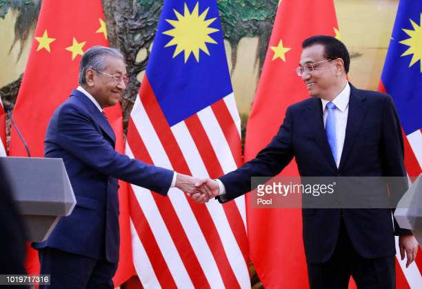 Malaysian Prime Minister Mahathir Mohamad shake hands with his Chinese counterpart Li Keqiang at the end of a press conference at the Great Hall of...