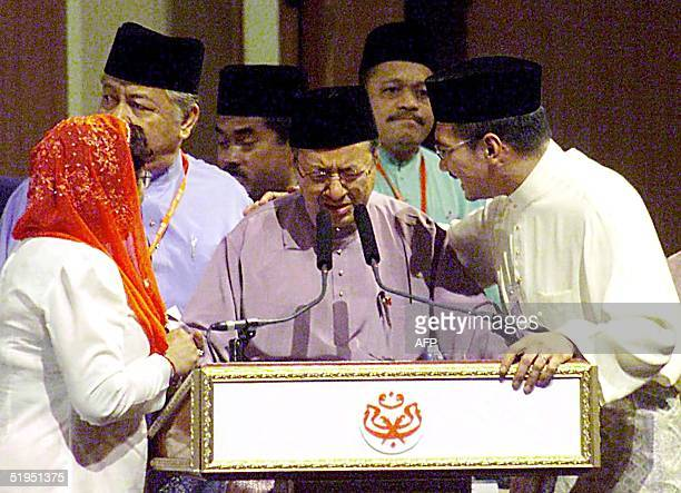 Malaysian Prime Minister Mahathir Mohammad being consoled by UMNO members after he announced the resignation during the United Malays National...