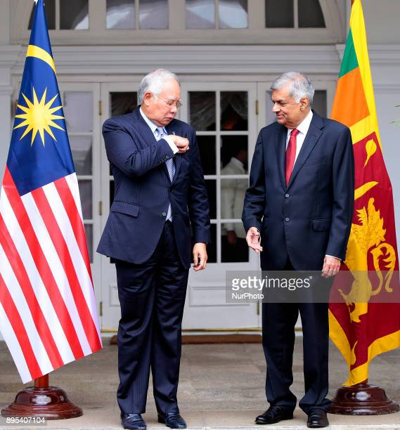 Malaysian Prime Minister Najib Razak folds a pocket square in his dress as Sri Lankan Prime Minister Ranil Wickramasinghe looks on during their...