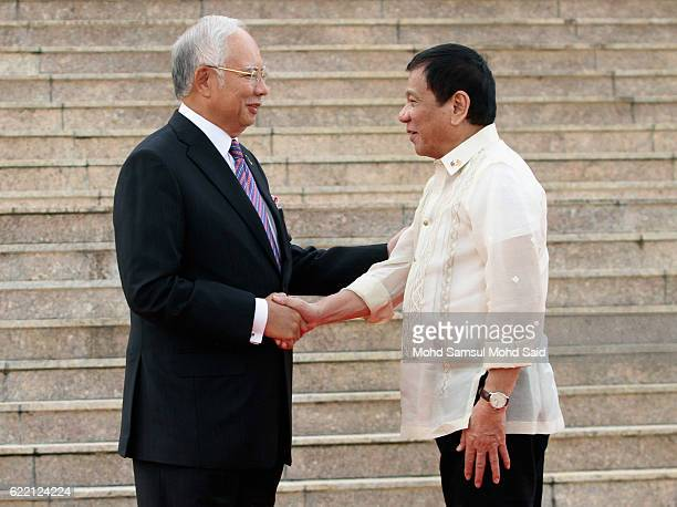 Malaysian Prime Minister Najib Razak shakes hand with Philippine President Rodrigo Duterte at the Prime Minister's office during an official visit on...